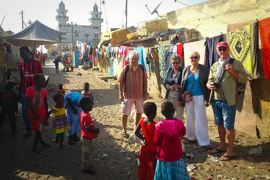 Les voyageurs rendent visite aux habitants d'un village avec leur guide Modou.