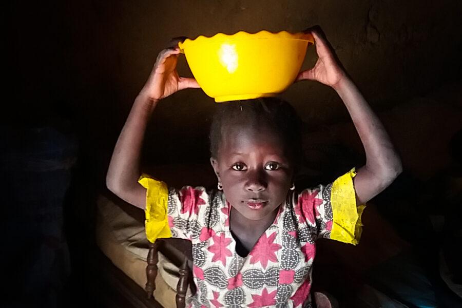 Une enfant tient un récipient jaune sur sa tête et regarde la caméra.