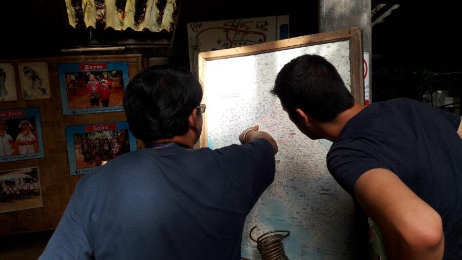 Un guide montrant une carte de la Thaïlande à un voyageur