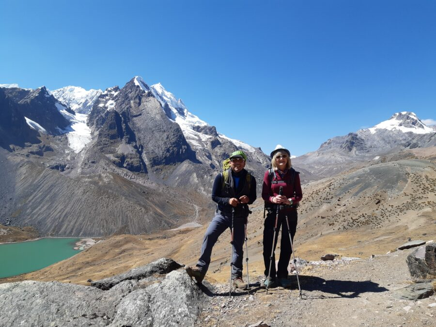 Une voyageuse et son guide avec des bâtons de randonnées en montagne au Pérou.