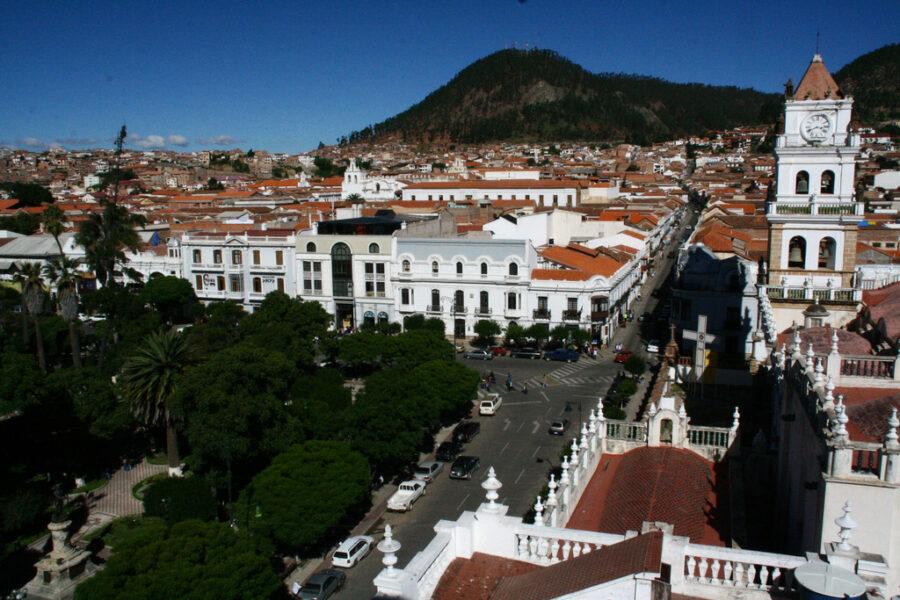 On a une vision aérienne de la ville de Sucre. On voit de nombreux bâtiments, des arbres et des montagnes au loin.