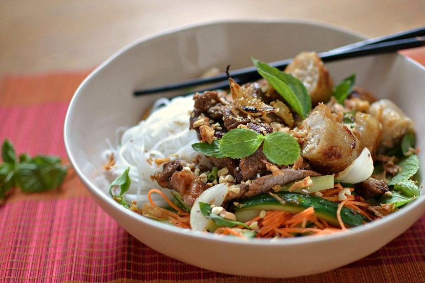 Un plat préparé dans un bol blanc avec des baguettes asiatiques