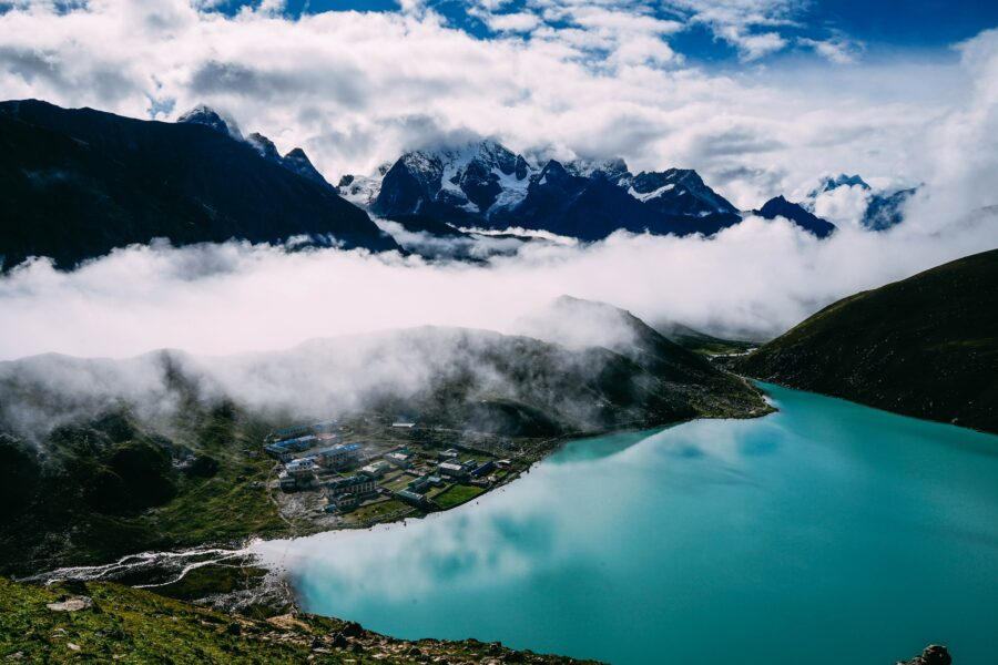 Depuis les montagnes, on voit un lac turquoise et un petit village juste en face.