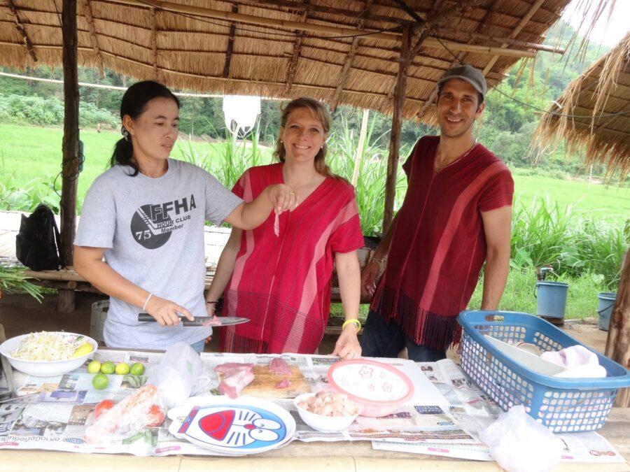 La femme du guide et les voyageurs cuisinent ensemble des plats thaïlandais.