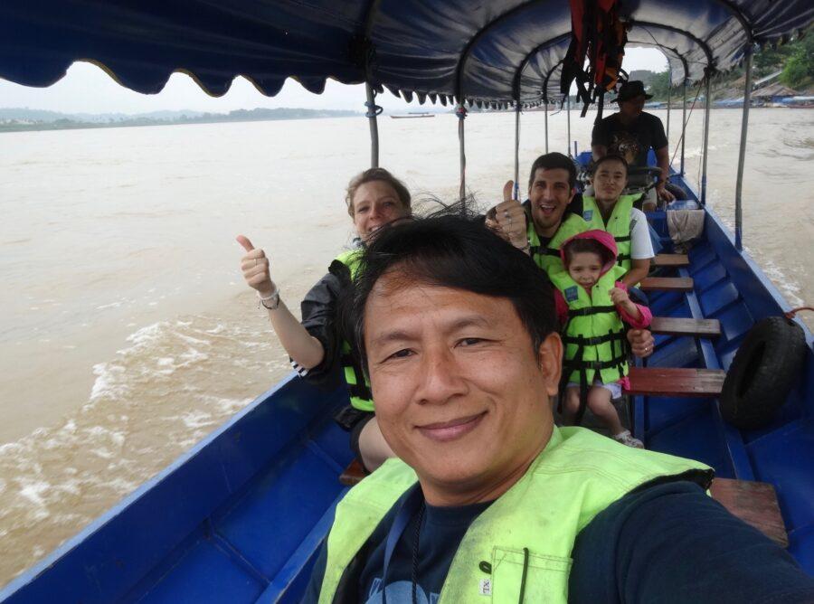 Le guide et les voyageurs prennent une photo sur un bateau qui traverse un lac.
