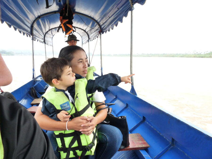 La femme du guide tient un des enfants dans les bras. Ils sont sur un bateau.