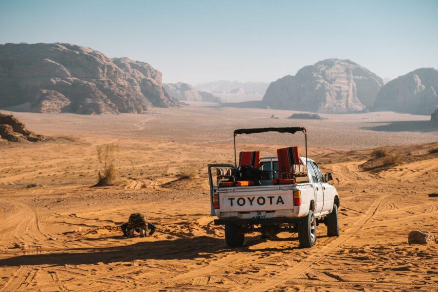 Un 4x4 roule dans le désert Jordanien en plein soleil.