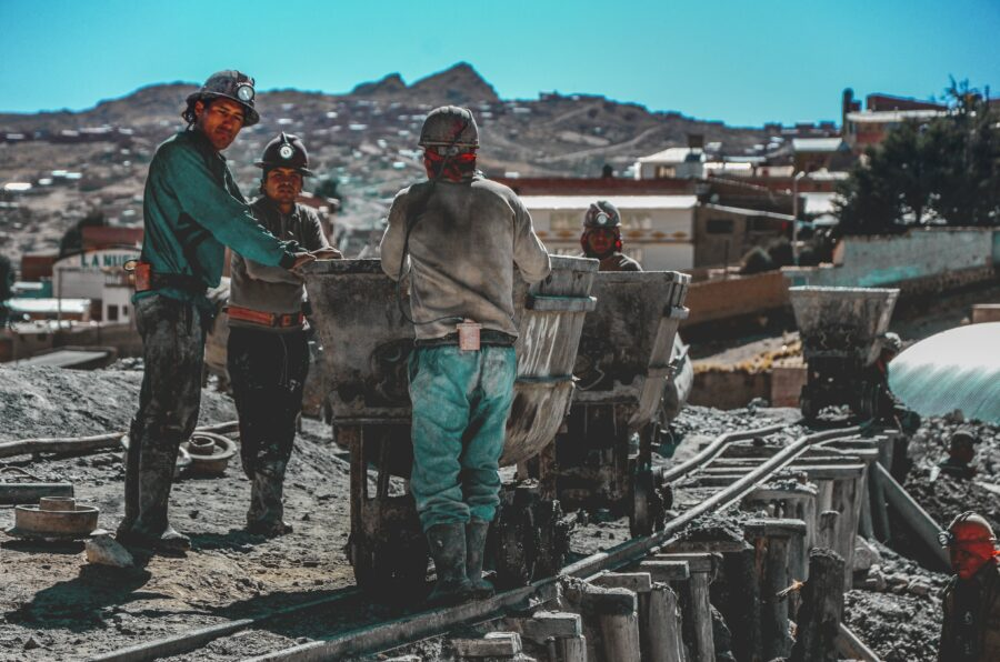 Des mineurs travaillent et déplace leurs affaires à l'aide des rails de train.