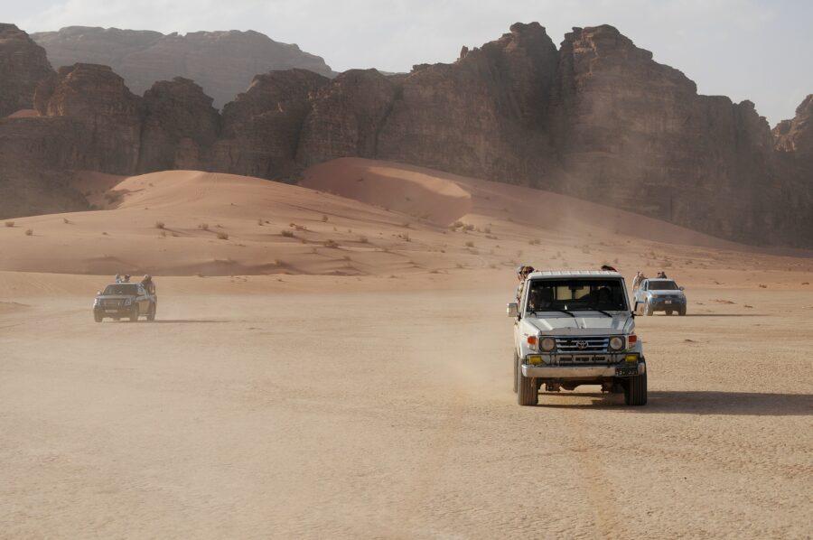 Trois 4x4 sont dans le désert et avancent dans la direction de la caméra. Jordanie guide indépendant Petra