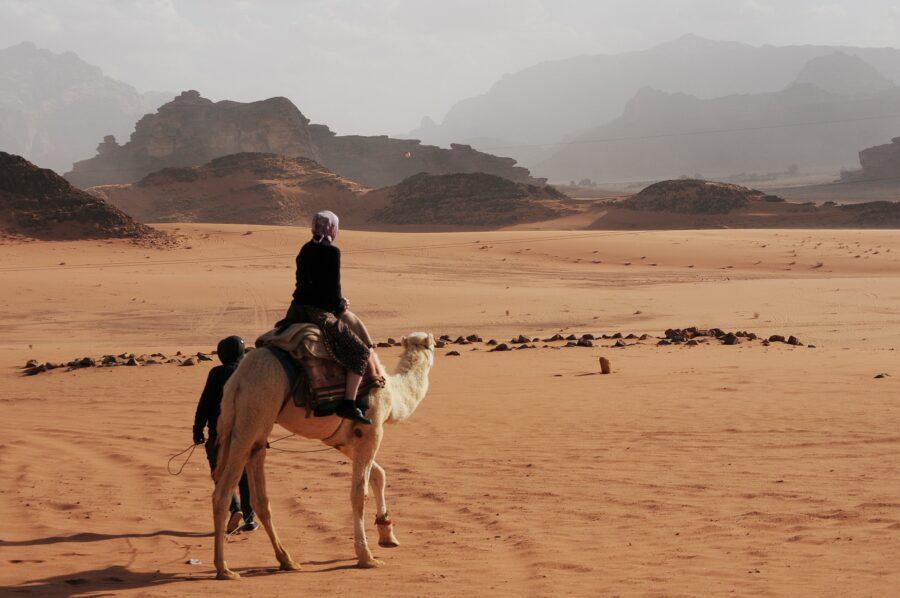 Une personne se trouve sur le dos d'un dromadaire qui avance dans le désert.
