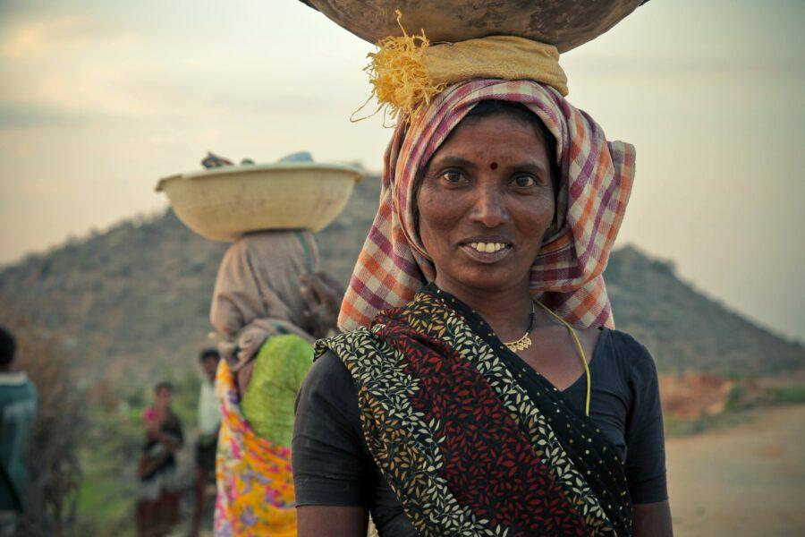 Une femme porte des affaires sur sa tête.