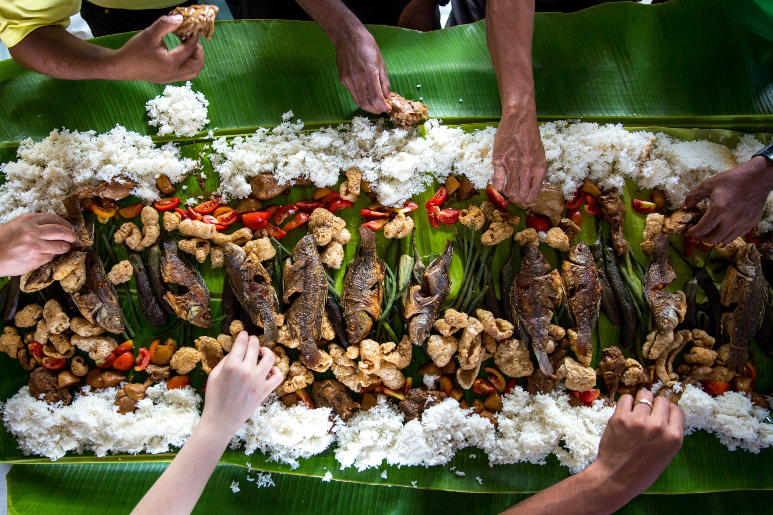 Un repas local mangé avec les mains. Il mange autour d'une grande table du riz, du poisson grillé et des légumes sur une feuille de bananier.