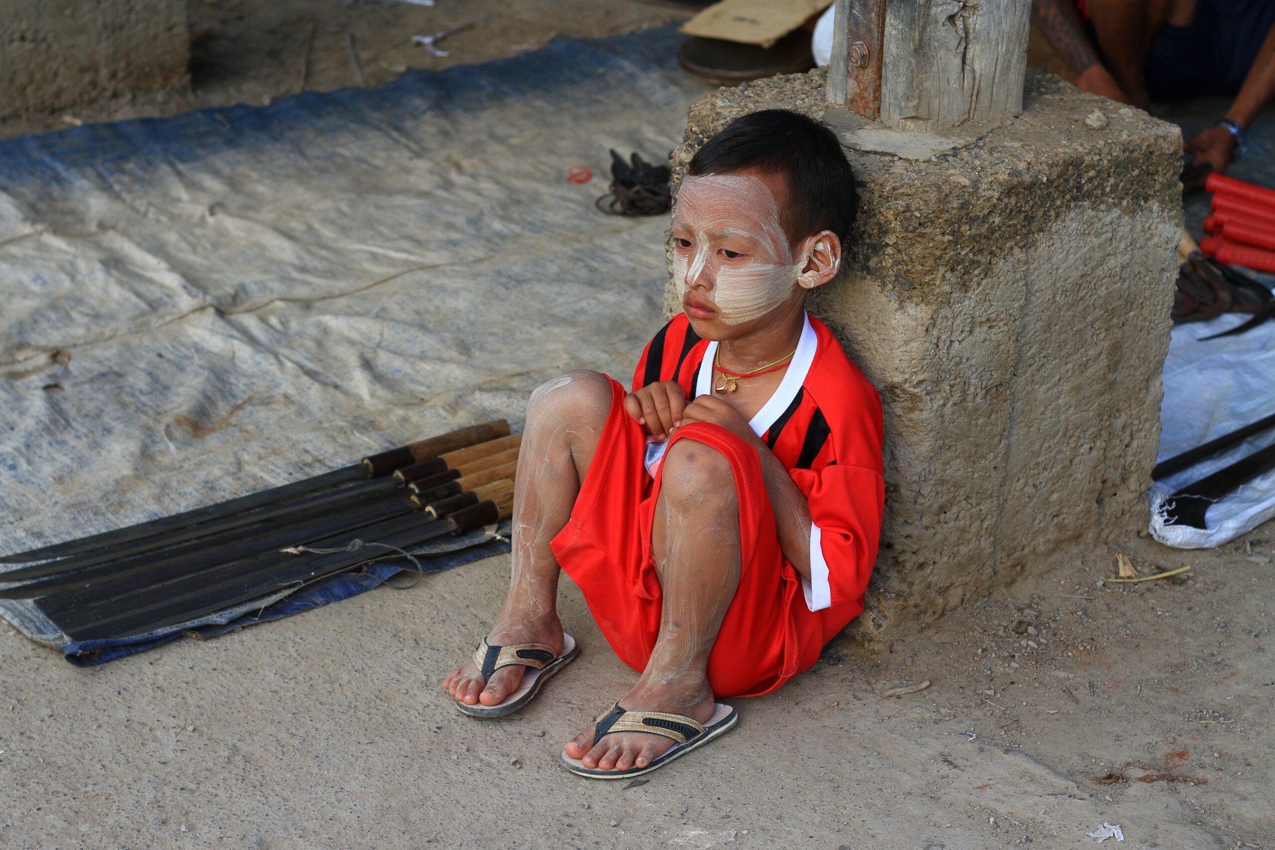 Un petit garçon habillé en rouge avec des tongs assis par terre contre un poteau avec de la boue sur le visage et les jambes pour se protéger du soleil Crème naturelle éco-responsable