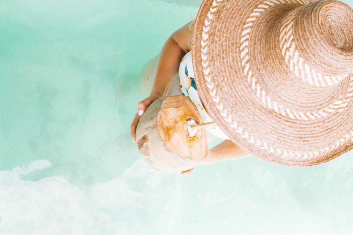 Une femme portant un chapeau en paille, les pieds dans l'eau buvant une noix de coco avec une paille en bois. Une paille en bois emmenée dans sa valise éco-responsable