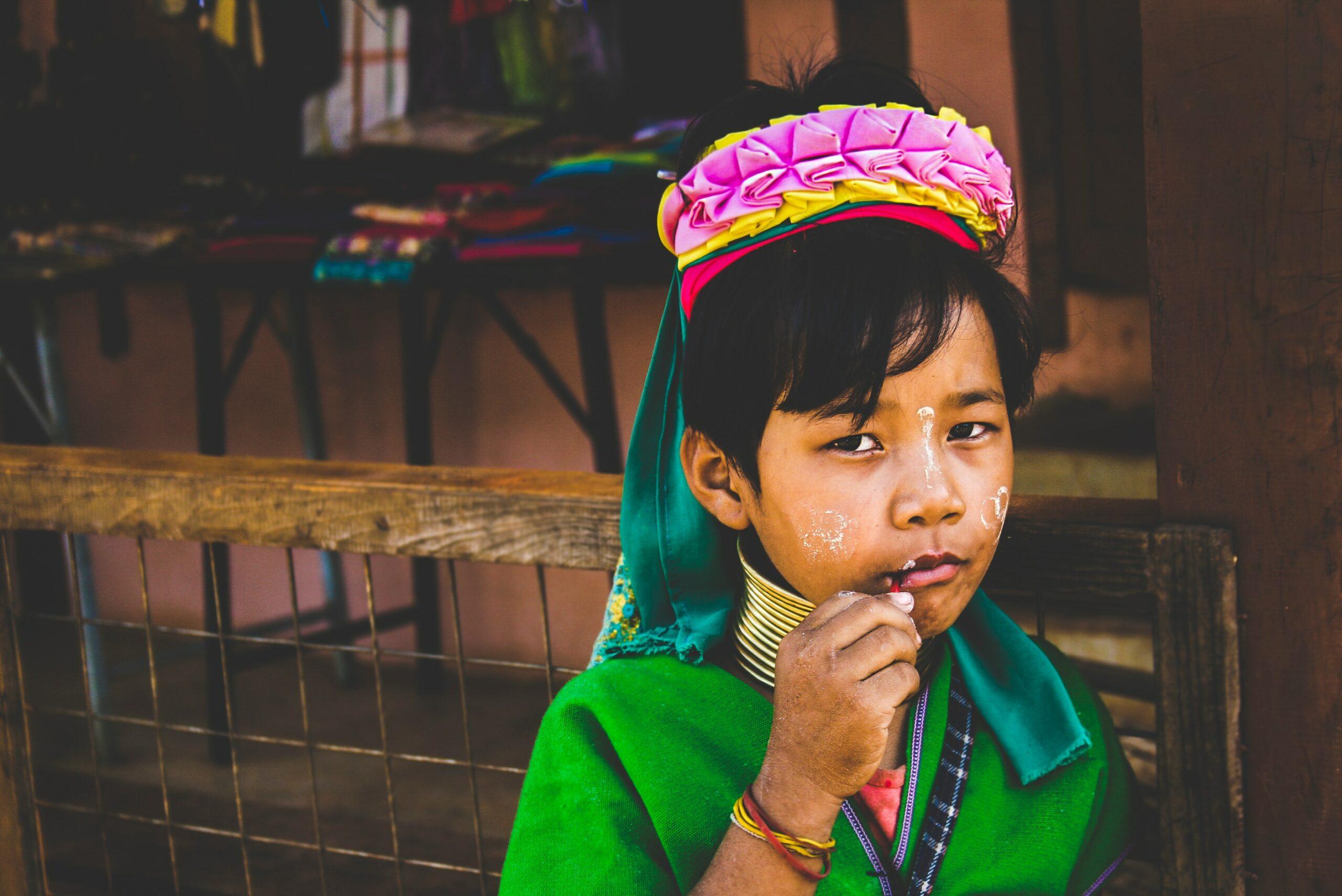 Un portrait coloré d'un enfant vêtu d'habits de fêtes. Il porte du vert du rose du jaune et du rouge. Permission donnée pour la photo