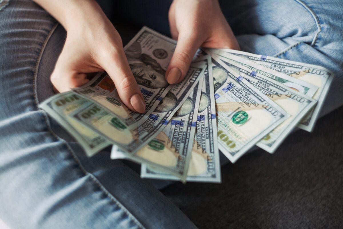 Une femme tenant des dollars. Calcul du budget