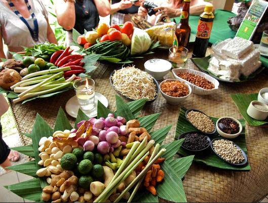 Un cours de cuisine avec plusieurs plats, des légumes, des condiments sur une table en bambou
