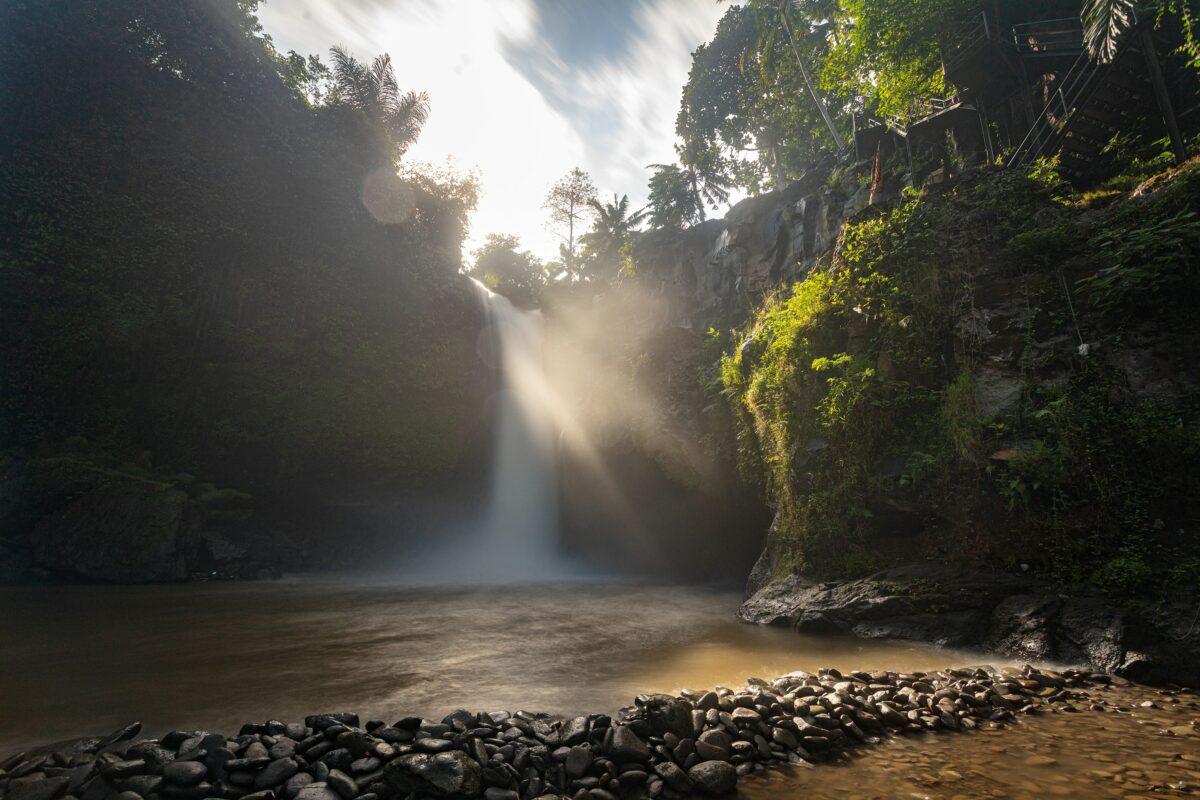 bali cascade vue du bas avec ciel bleu et rayon de soleil qui reflète sur l'eau