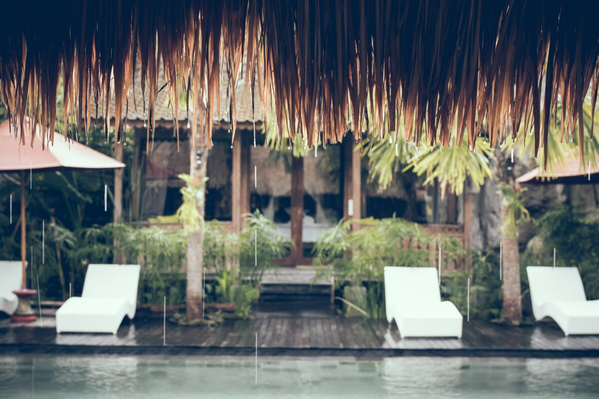 hotel Bali sous la pluie avec piscine et chaises longues sur une terrasse en bois