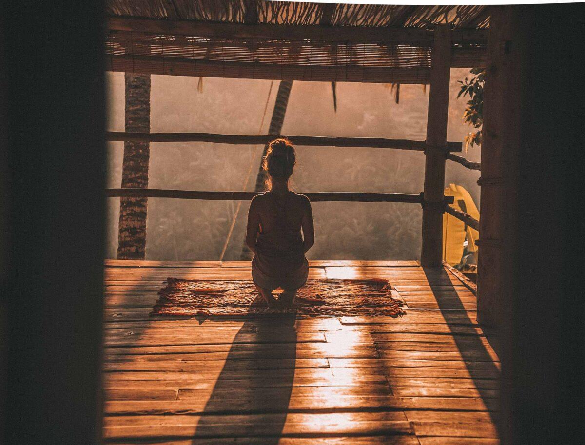 femme de dos assise en tailleur face à la jungle de Bali