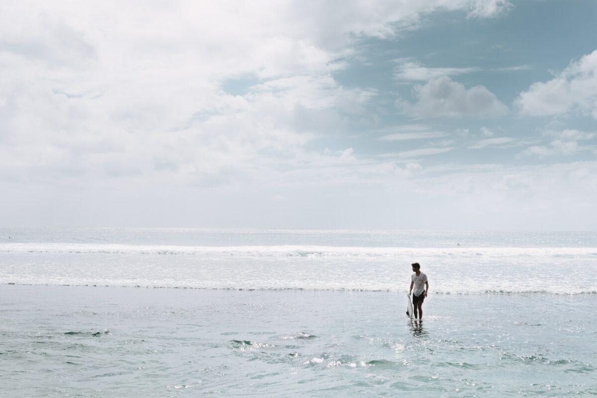 homme qui marche au bord de l'eau avec sa planche de surf à la main, ciel bleu à Bali
