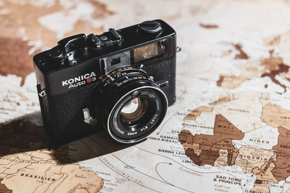 appareil photo argentique noir posé sur une carte du monde