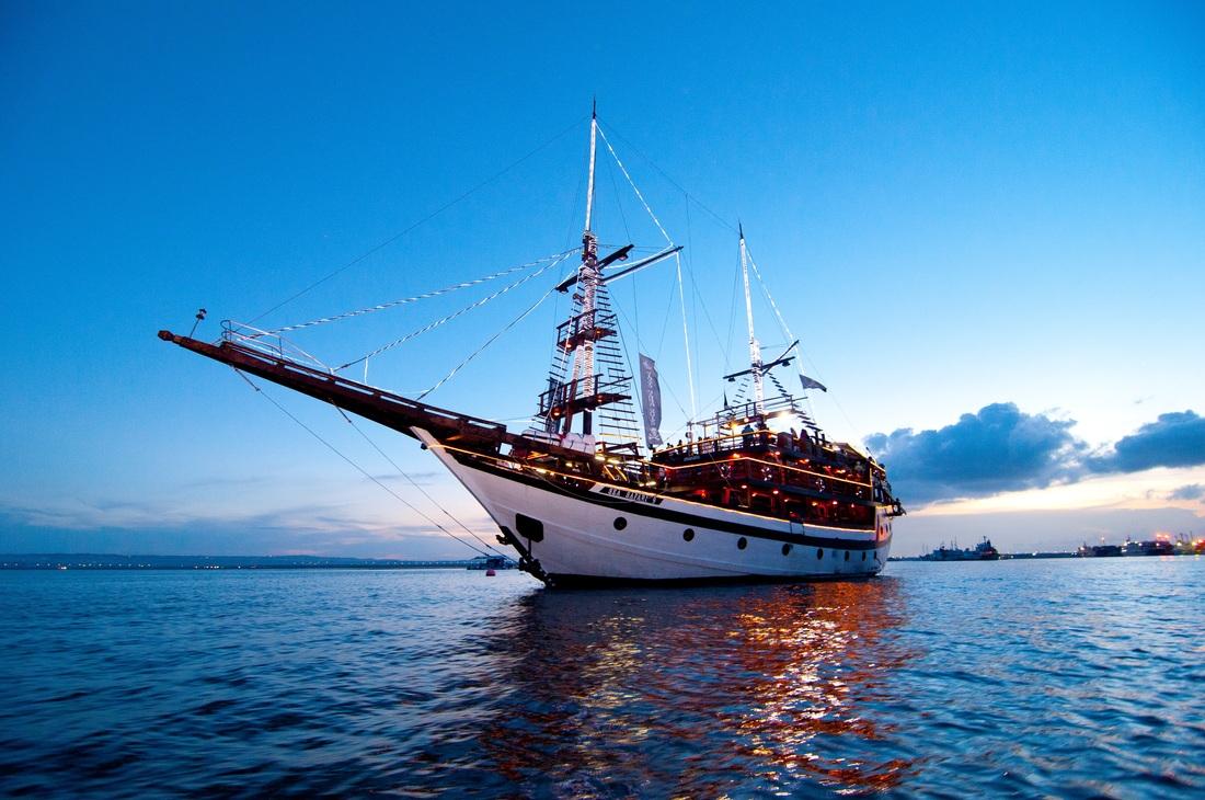 bateau pirate  de nuit le bateau est éclairé le ciel est bleu et il vogue sur l'eau